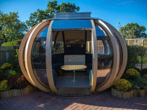 garden pods - photo of a big graden pod with glass, seats and a table.