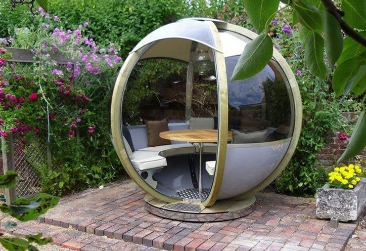 garden pods - photo of rotating seater garden pod with table and glass walls.