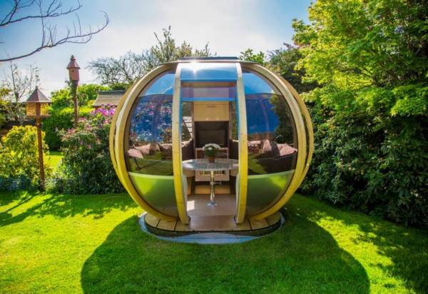 garden pods - photo of a garden pod with glass walls, seater and table in a backgarden.